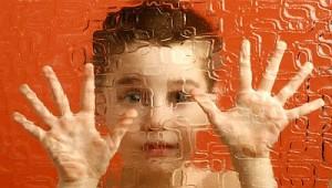 autista kisfiú üvegfal mögött néz át