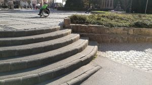 Budapest, Pesterzsébet Központ, felhasználói tesztelés és mérés, tapasztalati szakértővel és rehabilitációs szakmérnökkel. A kockakőburkolat akadálymentes szempontból nem helyes választás, az elfogyó és korlát nélküli lépcsőfokok balesetveszélyesek. 2018. Forrás: ETIKK