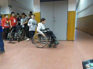 5. osztályos iskolások kerekesszékkel közlekednek az iskola folyosóján
